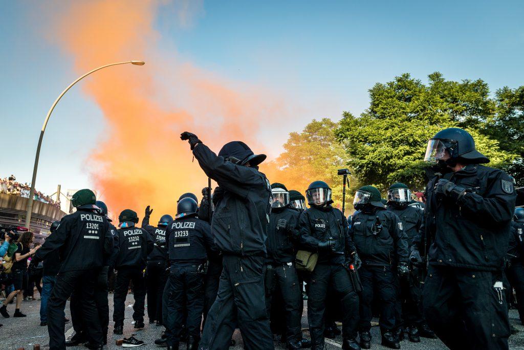 """Behelmte Polizisten sammeln sich wieder, nachdem die """"Welcome to hell"""" Demo eskalierte."""