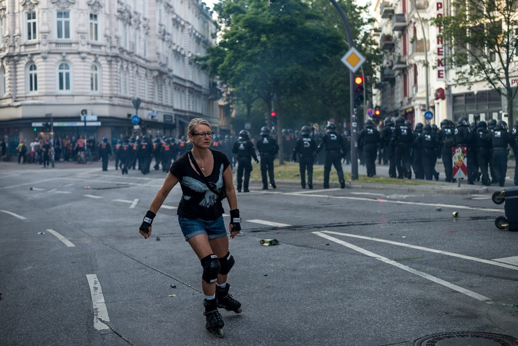 Eine Skaterin auf dem Schulterblatt, während eine Hunderschaft der Polizeiversucht ins Schanzenviertel vorzurücken.
