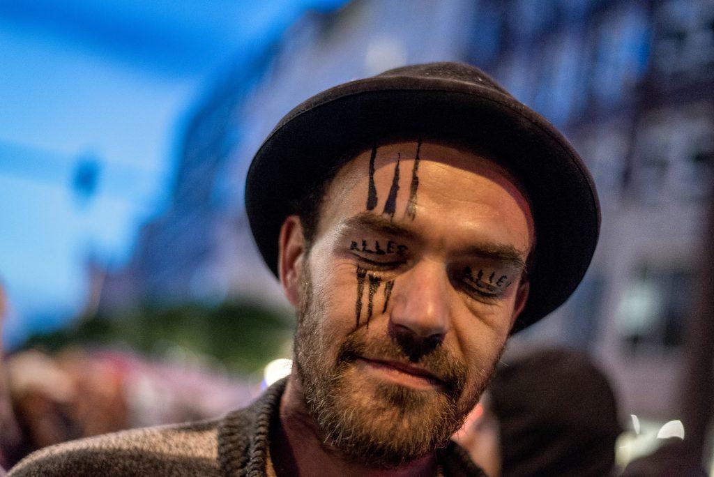 """Ein Mann bei der Abschlusskundgebung der """"LIeber tanz ich als G20"""" Demo im Clockwork Orange Outfit. Auf seinen Augenlidern steht """"ALLES ALLEN"""". Die Demo endete friedlich, nach kleinem Gerangel."""