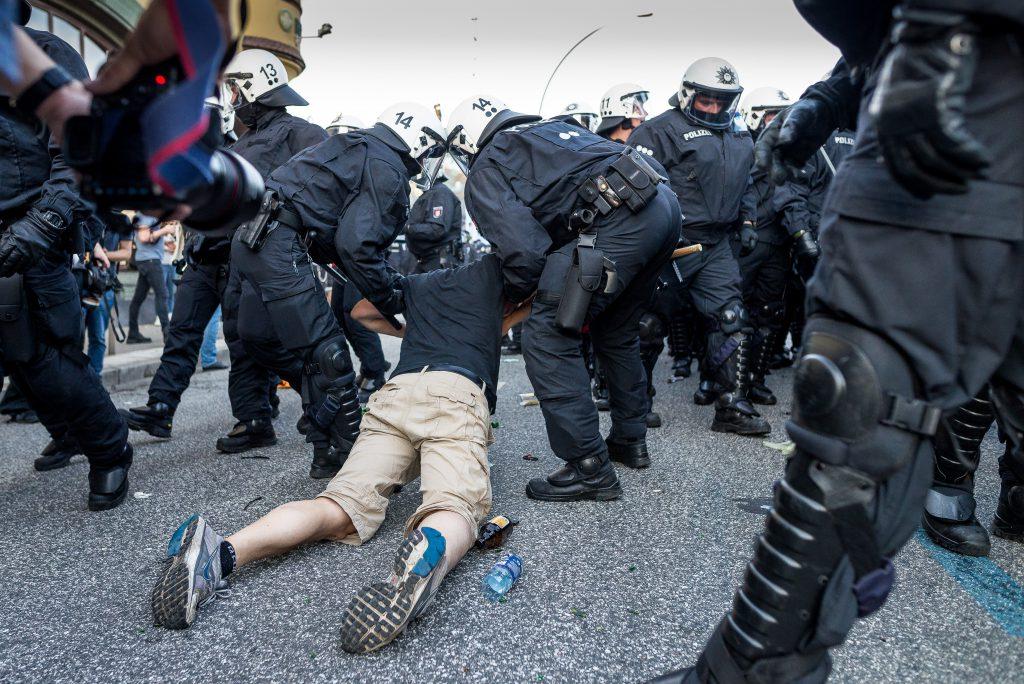 Ein zu Boden gegangener Demonstrant wird von zwei Polizisten an die Seite gebracht.