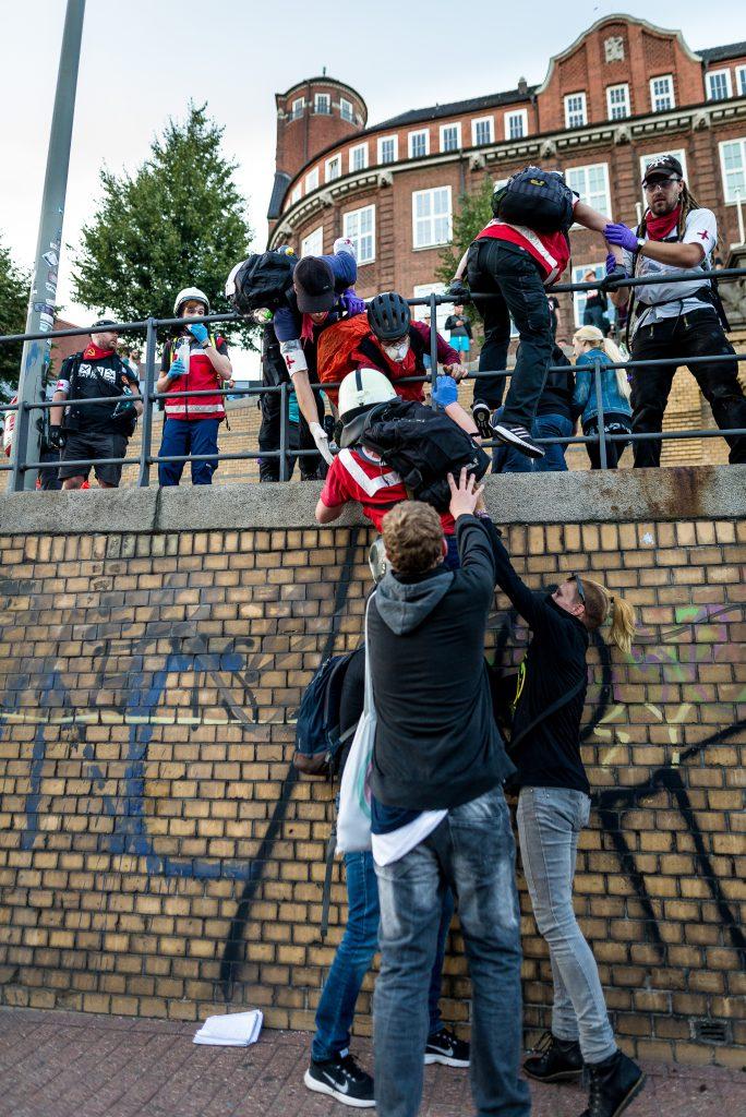 Demonstranten helfen Demo-Sanitätern eine Mauer hoch zu kommen, nachdem die Polizei die Straße absperrte.