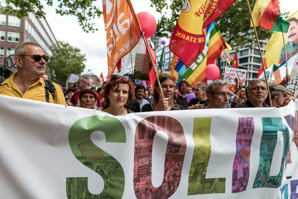 """Katja Kipping(Vorsitzende, DIE LINKE) hinter dem Fronttransparent der Großdemo am 8.7. Auf dem Transparent steht """"Solidarity instead of G20""""."""