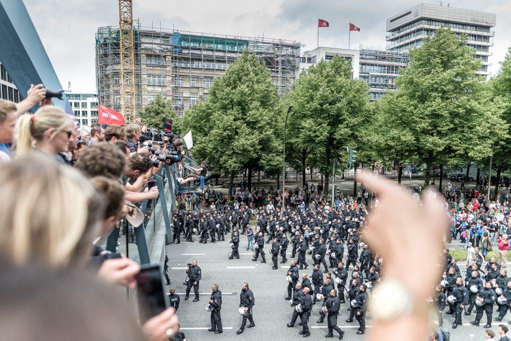 """Die vordere Reihe der Großdemonstration """"Grenzenlose Solidarität statt G20"""" am Samstag den 8.7, hinter einer Hundertschaft der Polizei auf der Willy-Brandt-Straße. Auf der Brücke zahlreiche Journalisten."""