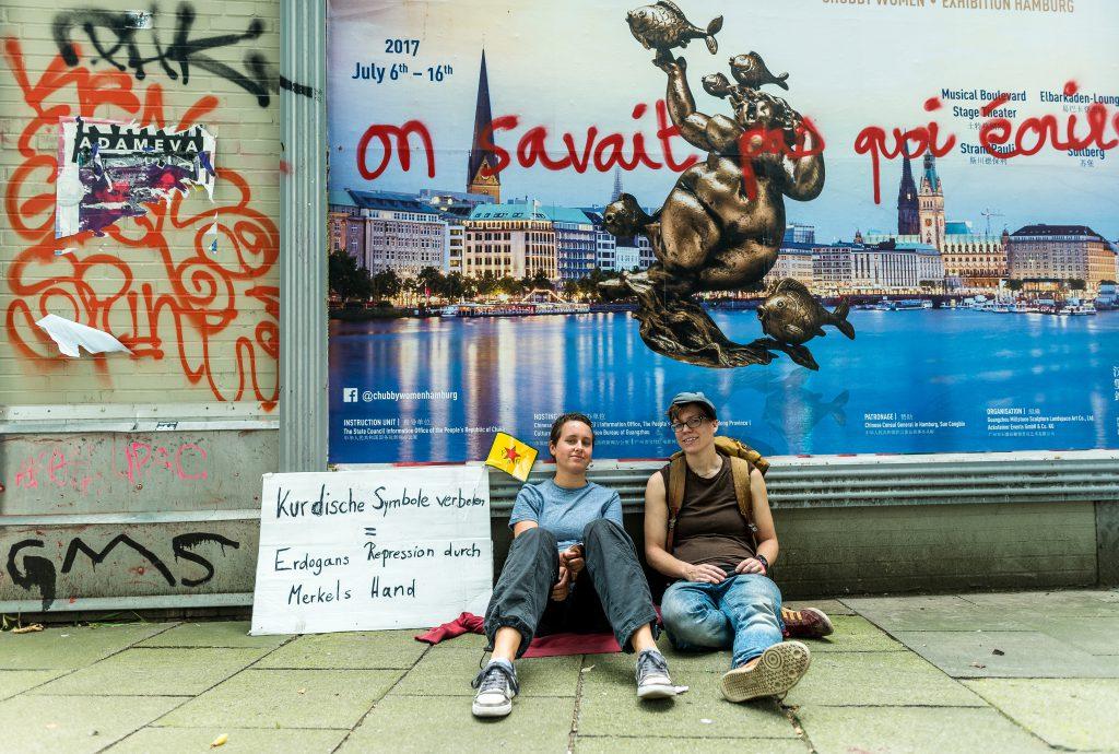 """Zwei Demonstranten ruhen sich am Rande der Großdemo am 8.7 aus. Auf dem Werbeplakat im Hintergrund steht auf Französisch """"Wir wussten nicht, was wir schreiben sollten."""""""