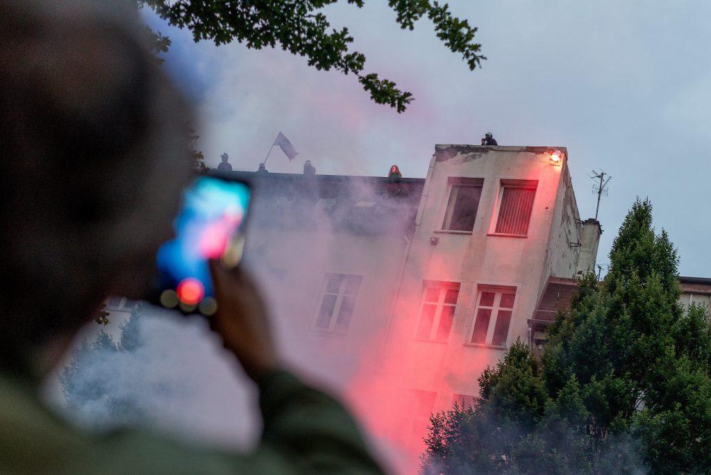 """Ein Mann fotografiert mit seinem Smartphone eine Fahnen und Pyro Aktion auf dem Dach des Gängeviertels während der """"Lieber tanz ich als G20""""-Demonstration."""